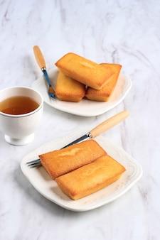 Heerlijke french pastry financier cake, kleine cake met boter, geserveerd met thee.