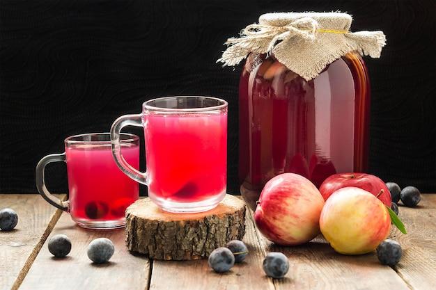 Heerlijke fruitcompote uit blik van appels en sleedoorn in glazen pot en mokken