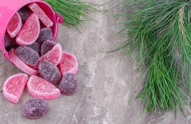 Heerlijke fruitgelei snoepjes uit roze emmer op steen.