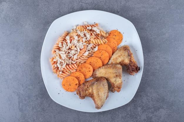 Heerlijke fusilli pasta en kippenvleugels op witte plaat.
