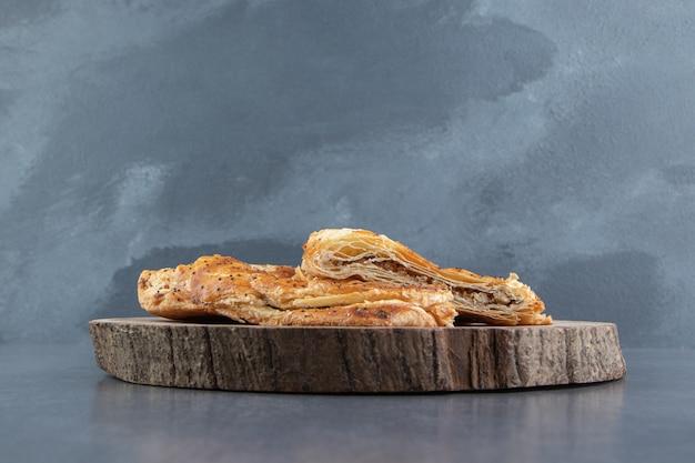 Heerlijke gebakjes gevuld met vlees op houten stuk.