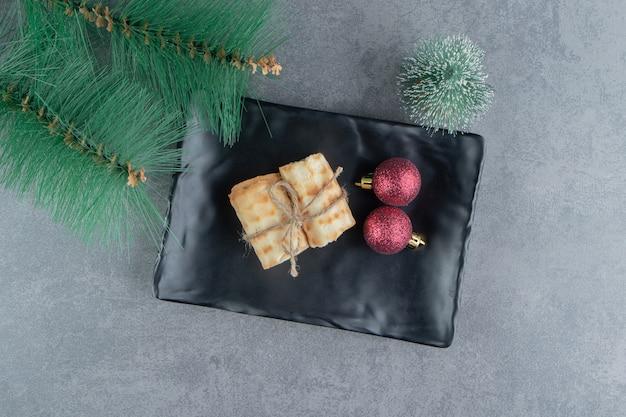 Heerlijke gebakjes met kerstballen op een donkere plaat