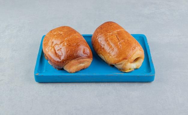 Heerlijke gebakjes met worstjes op blauw bord.
