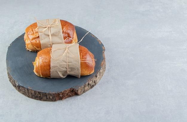 Heerlijke gebakjes met worstjes op houten stuk.