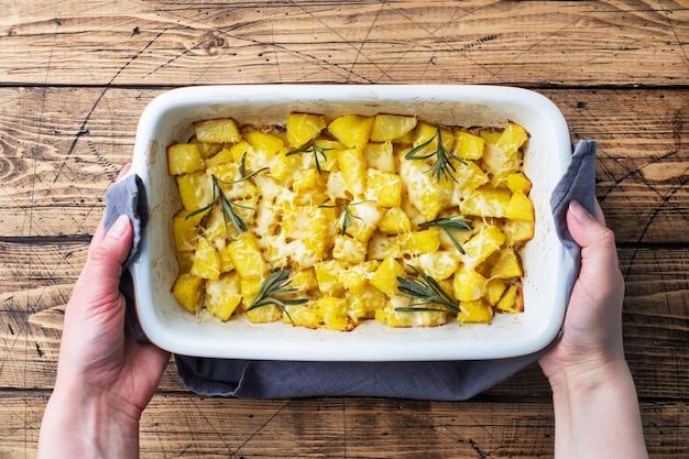 Heerlijke gebakken aardappelen met kruiden kaas en rozemarijn in een keramische bakplaat op een houten rustieke achtergrond.