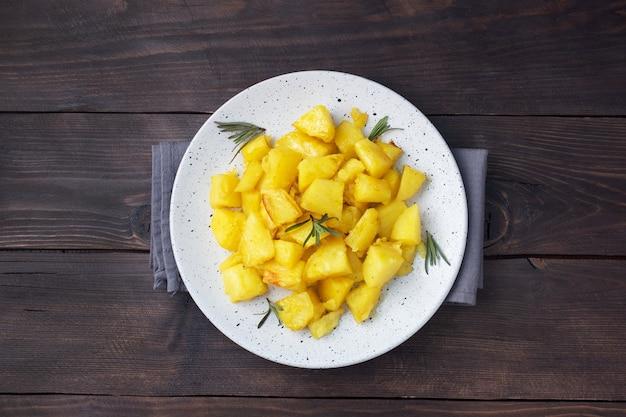 Heerlijke gebakken aardappelen met kruiden kaas en rozemarijn op een bord, een donkere houten tafel. ruimte kopiëren