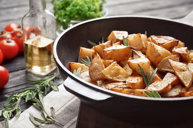 Heerlijke gebakken aardappelen met rozemarijn in pan op tafel