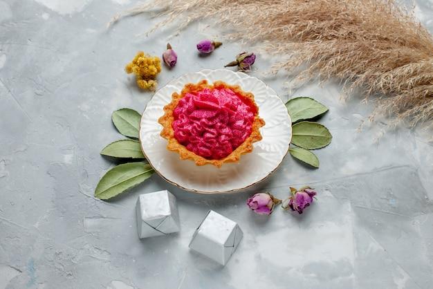 Heerlijke gebakken cake met roze room en chocolaatjes op licht bureau, zoete cake koekjes bakken cream tea