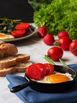 Heerlijke gebakken eieren in een pan met gebakken spinazie en champignons gelegen op een grijze tafel. detailopname.