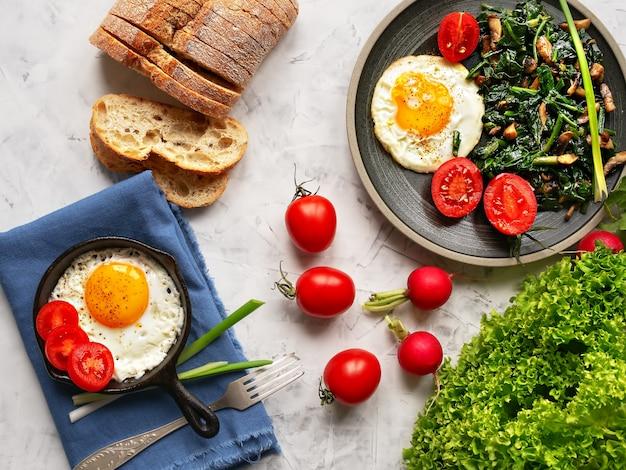 Heerlijke gebakken eieren op een bord en in een kleine pan met gebakken spinazie en champignons gelegen op een grijze tafel. bovenaanzicht.