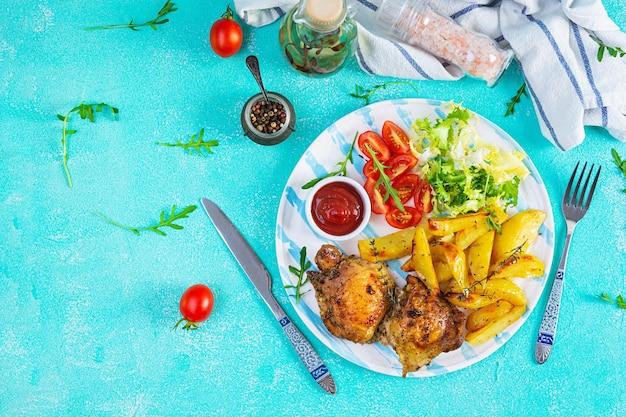 Heerlijke gebakken kip met aardappelen op blauw. bovenaanzicht