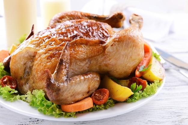 Heerlijke gebakken kip op bord op tafel op lichte ondergrond