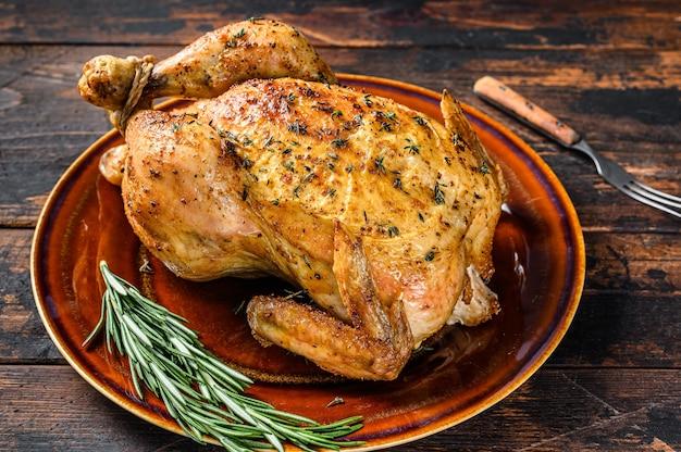 Heerlijke gebakken kip op houten tafel. donkere achtergrond. bovenaanzicht.