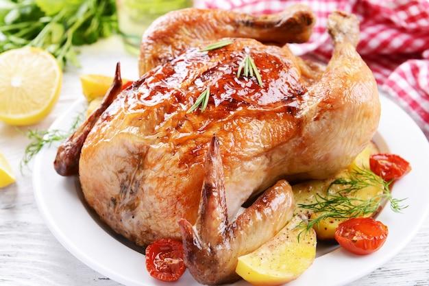 Heerlijke gebakken kip op plaat op tafel close-up
