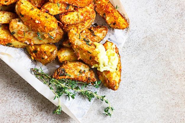 Heerlijke gebakken krokante aardappelen met tijm en saus in een papieren zak om mee te nemen. fastfood op straat.