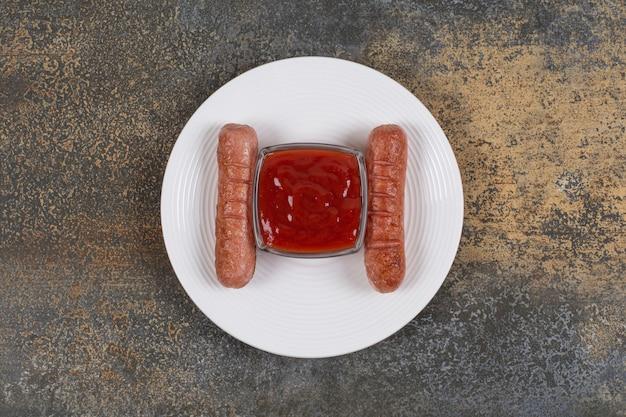 Heerlijke gebakken worstjes en ketchup op witte plaat.