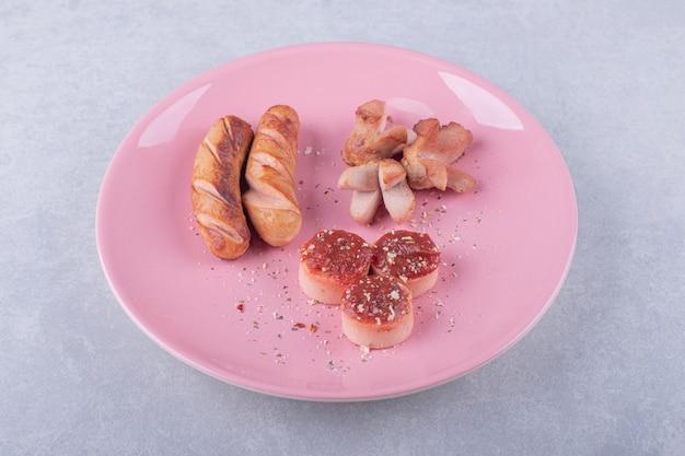 Heerlijke gebakken worstjes met ketchup op roze plaat.