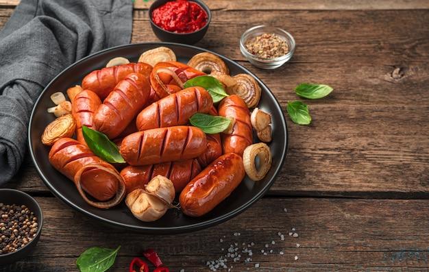 Heerlijke gebakken worstjes op de achtergrond van saus en kruiden