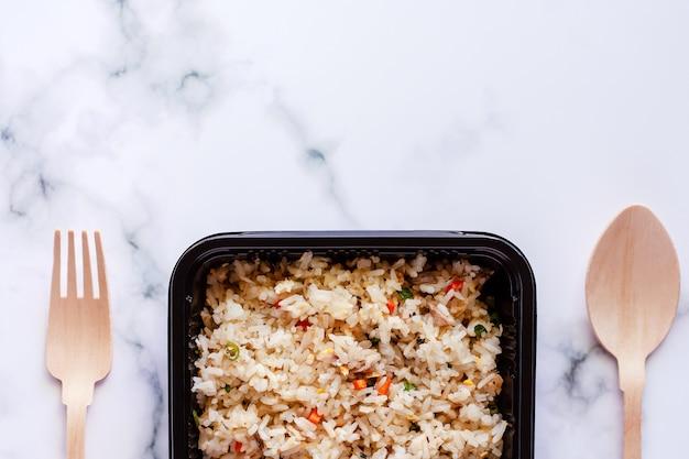 Heerlijke gebraden rijst in lunchdoos met houten lepel en vork op marmeren achtergrond
