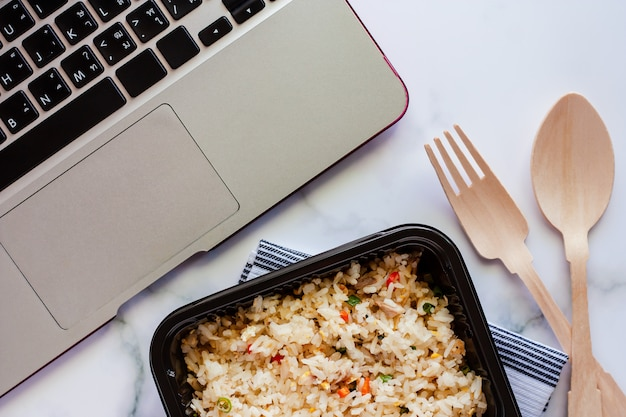 Heerlijke gebraden rijst in lunchdoos op napery met houten lepel en vork en computerlaptop op het werk