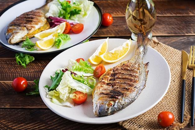 Heerlijke gegrilde dorado of zeebrasem vis met salade, kruiden, gegrilde dorada op een houten tafel