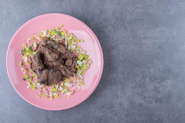 Heerlijke gegrilde kebab op roze plaat.