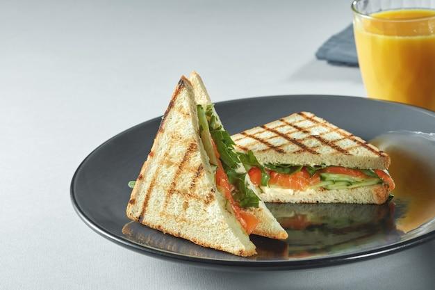 Heerlijke gegrilde sandwiches op platen met jus d'orange op de witte tafel