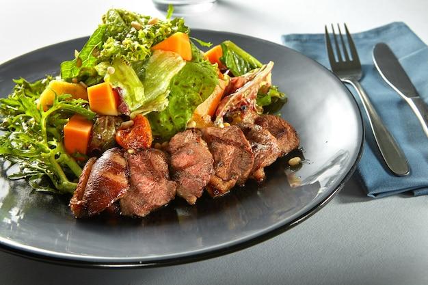 Heerlijke, gegrilde vleeseend met geroosterde pompoen en verse groene kruidensalade op een bord