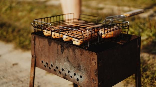 Heerlijke gegrilde worstjes rustend op het ijzeren rooster van een draagbare barbecue boven gloeiende kolen terwijl ze tot in de perfectie koken