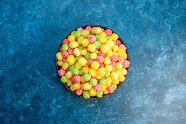 Heerlijke gekleurde snoepjes in een kleine bruine pot op blauwe achtergrond