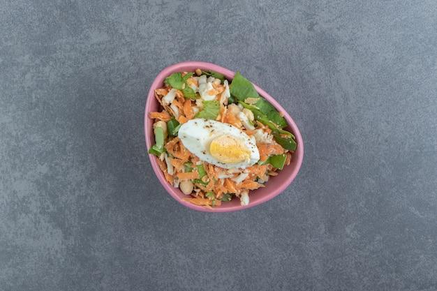 Heerlijke gekookte eieren en verse salade in roze kom.