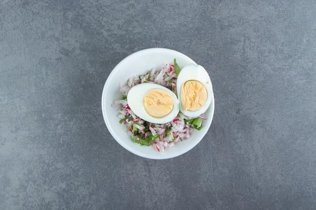 Heerlijke gekookte eieren en verse salade in witte kom.