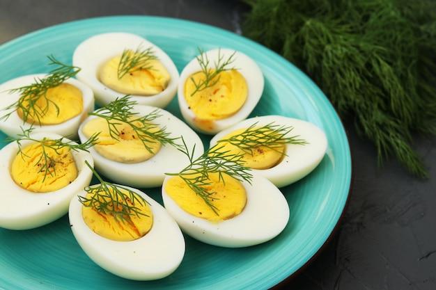 Heerlijke gekookte eieren met dille op een bord in het donker