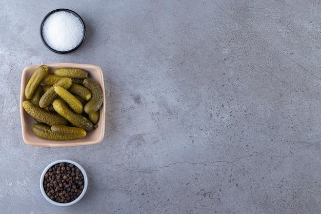Heerlijke gemarineerde ingelegde komkommers op stenen tafel.