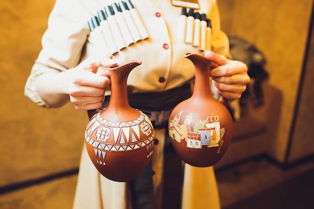 Heerlijke georgische lavash met erachter glas van drank en persoonsholdingskleikruik.