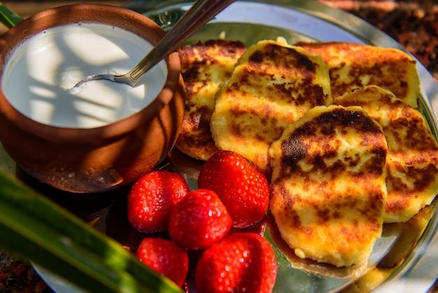 Heerlijke geroosterde syrniki of beignets, verse room in een pot en rijpe aardbeien, close-up. geweldig ontbijt buiten op zonnige ochtend.