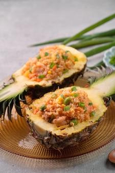 Heerlijke gesneden ananas geserveerd als een kom containerboot gevuld met verse ananas, tomaat, gebakken rijst met zeevruchten.