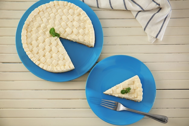 Heerlijke gesneden cheesecake op houten tafel
