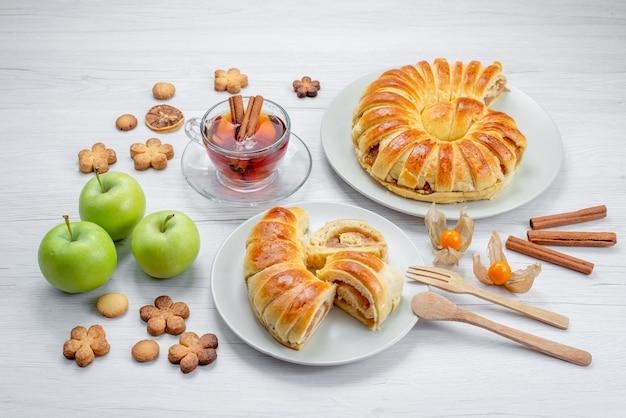 Heerlijke gesneden gebakjes binnen plaat met het vullen samen met groene appelthee en koekjes op wit bureau, het koekjessnoepje van het gebakjekoekje