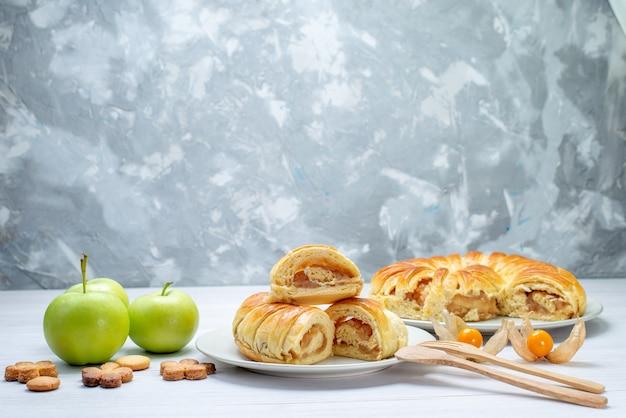 Heerlijke gesneden gebakjes binnen plaat met vulling samen met appels en koekjes op witte vloer gebak koekjeskoekje zoete suiker