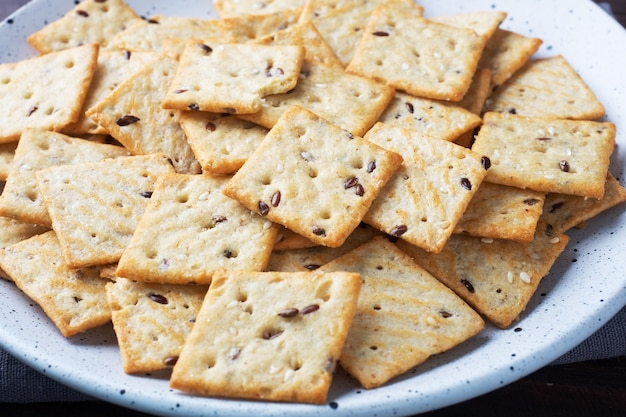 Heerlijke gezonde koekjescrackers met lijnzaad en sesamzaden op een plaat. achtergrond van een gezonde snack, close-up.