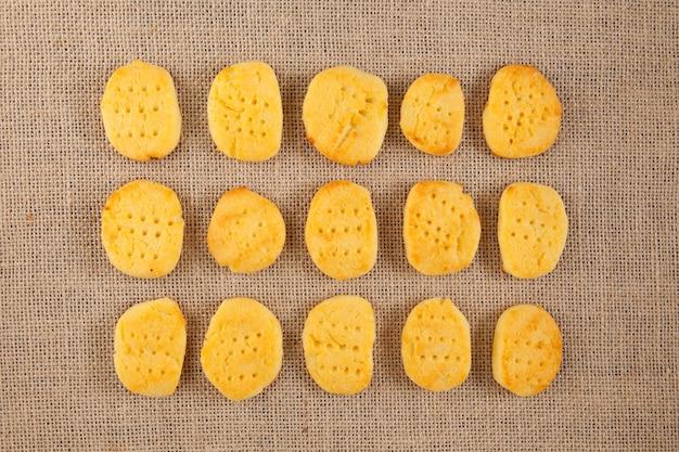 Heerlijke glutenvrije zelfgemaakte koekjes liggen in even rijen op jute.