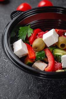 Heerlijke griekse salade met tomaten, olijven en verse kruiden, een frisse salade op het menu van een fastfoodrestaurant op een donkere stenen tafel. gezonde optie van fast food.