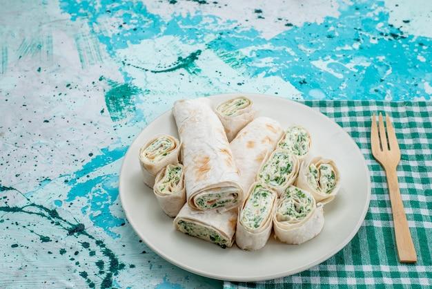 Heerlijke groentebroodjes geheel en in plakjes gesneden op helderblauwe, voedselmaaltijdrolgroente
