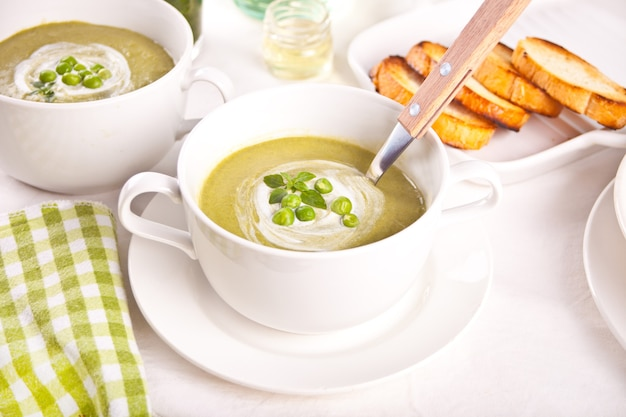 Heerlijke groentesoep met aardappel, broccoli, doperwten en spinazie op tafel