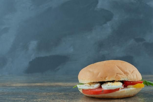Heerlijke hamburger met eieren en tomaten op marmeren achtergrond