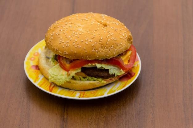 Heerlijke hamburger of sandwich op plaat op houten tafel. zelfgemaakte hamburger op hout achtergrond