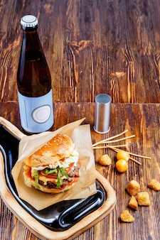 Heerlijke hamburger, snacks en bier op een houten tafel