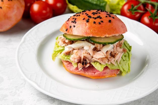 Heerlijke hamburger van roze deeg met zalm op een witte plaat