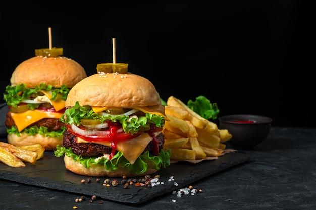 Heerlijke hamburgers met rundvlees, groenten en kaas op een zwarte achtergrond met frietjes. zijaanzicht, kopieer ruimte.